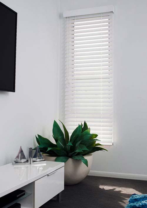 White timber Venetian blind filtering light in a living room