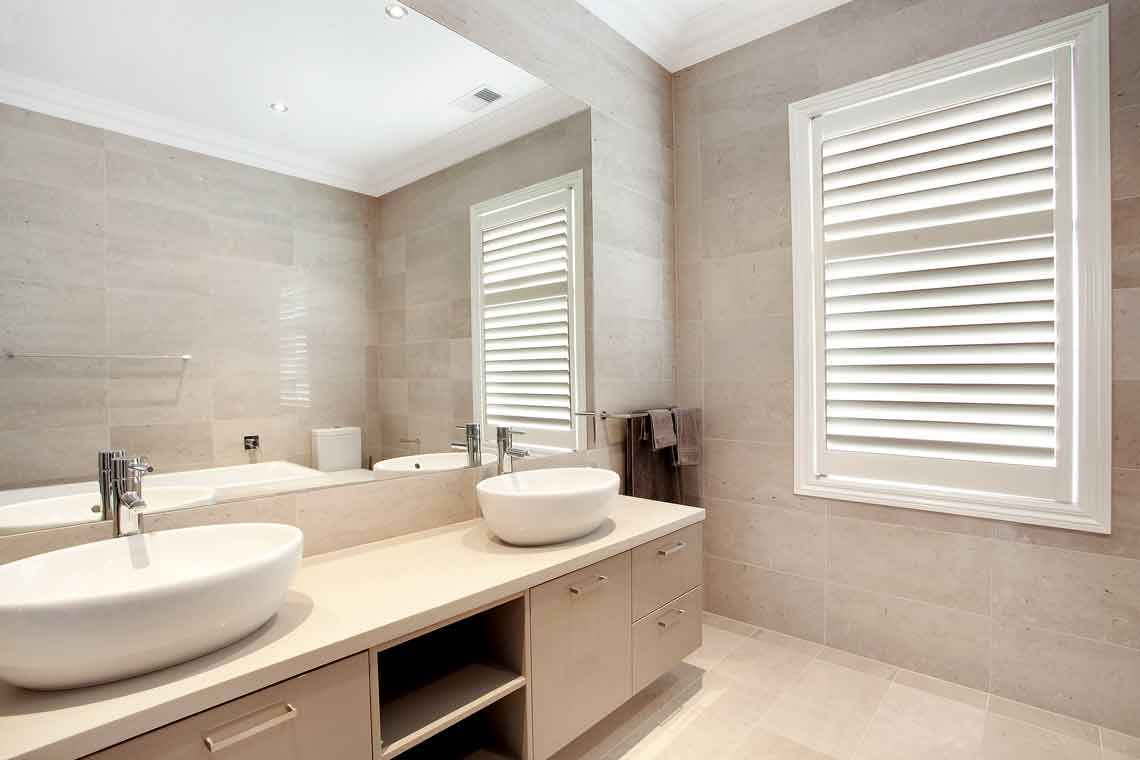 White plantation shutter fitted to a bathroom window