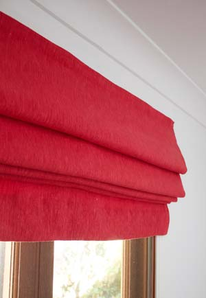Bright red roman blind fitted over a study window